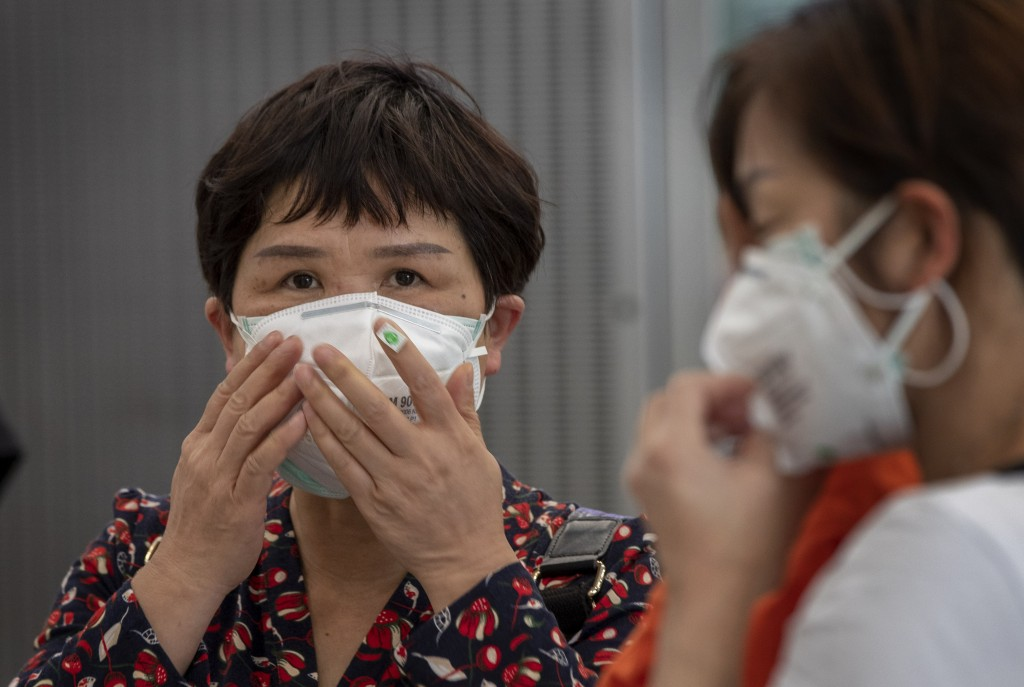 Tourists from Wuhan, China, some with double-layered face masks, stand in a line for a charter flight back to Wuhan at the Suvarnabhumi airport, Bangk...