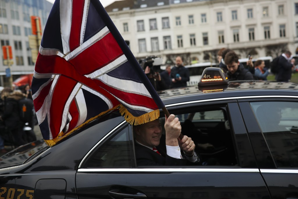 British MEP Jonathan Bullock holds an Union flag as he leaves with other party members the European Parliament in Brussels to take the Eurostar train ...