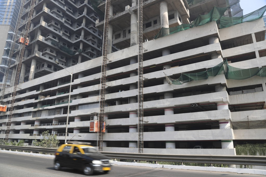 File- In this Tuesday, Jan. 21, 2020, file photo, a car drives past an under-construction building in Mumbai, India, Tuesday, Jan. 21, 2020. India's g...