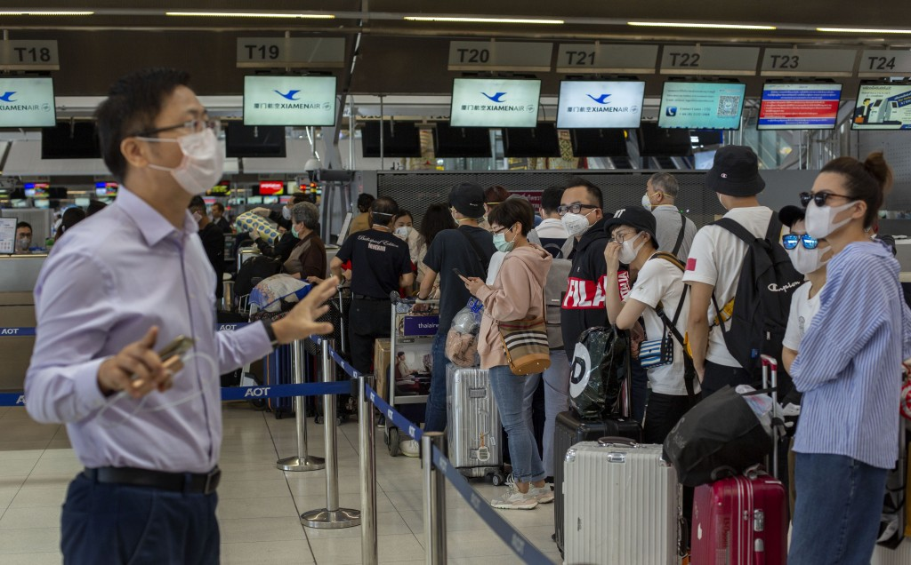 An airport official speaks to tourists from Wuhan, China, waiting for a charter flight back to Wuhan at the Suvarnabhumi airport, Bangkok, Thailand, F...