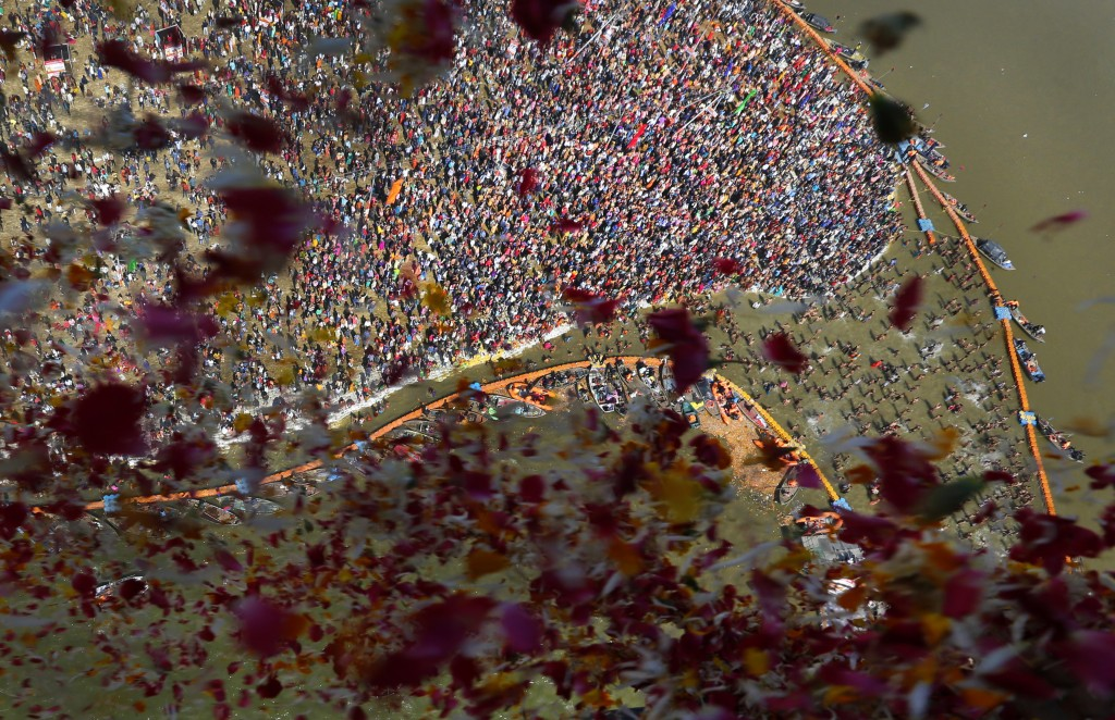 In this Friday, Jan. 24, 2020, file photo, government officials throw flowers from a helicopter onto thousands of Hindu devotees performing rituals at...