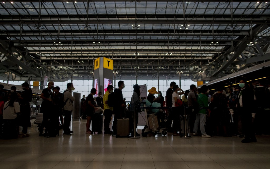 Tourists from Wuhan, China, line up to get a seat on a charter flight returning to Wuhan at Suvarnabhumi airport, Bangkok, Thailand, Friday, Jan. 31, ...