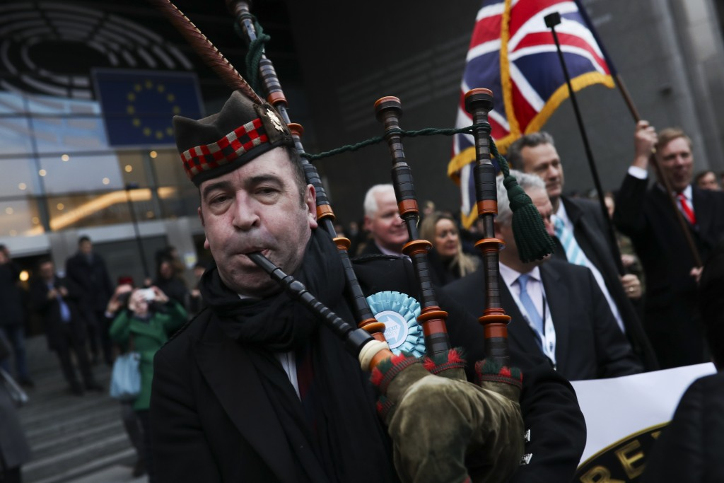 British MEP's carry a Union flag as they march out of European Parliament with their luggage in Brussels to take the Eurostar train back to Britain, F...