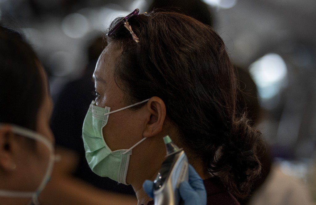 A health worker checks the temperature of tourist from Wuhan, China, as she waits for a charter flight back to Wuhan at the Suvarnabhumi airport, Bang...