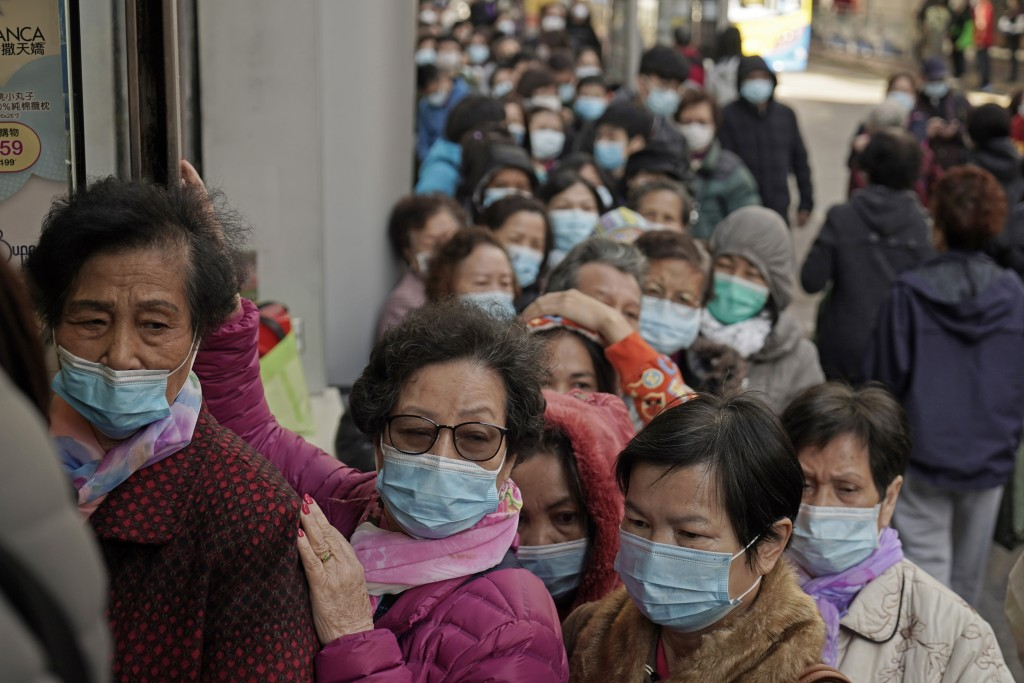 In this Thursday, Jan. 30, 2020, file photo, people queue up to buy face masks at a cosmetics shop in Hong Kong. Hong Kong cut off rail service to mai...