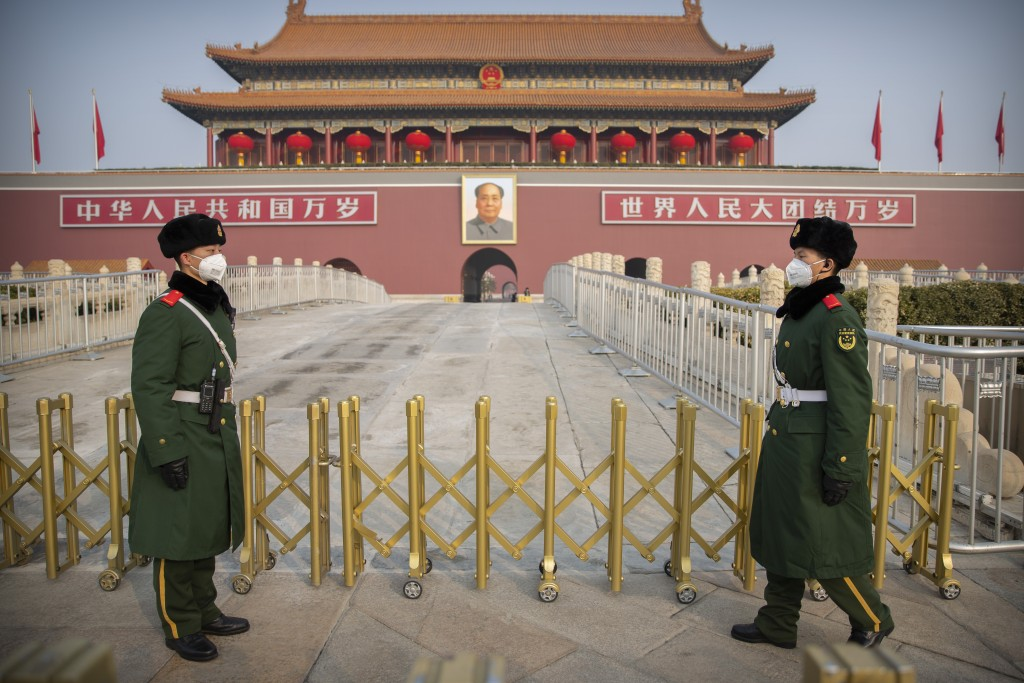 In this Monday, Jan. 27, 2020, file photo, paramilitary police wear face masks as they stand guard at Tiananmen Gate adjacent to Tiananmen Square in B...