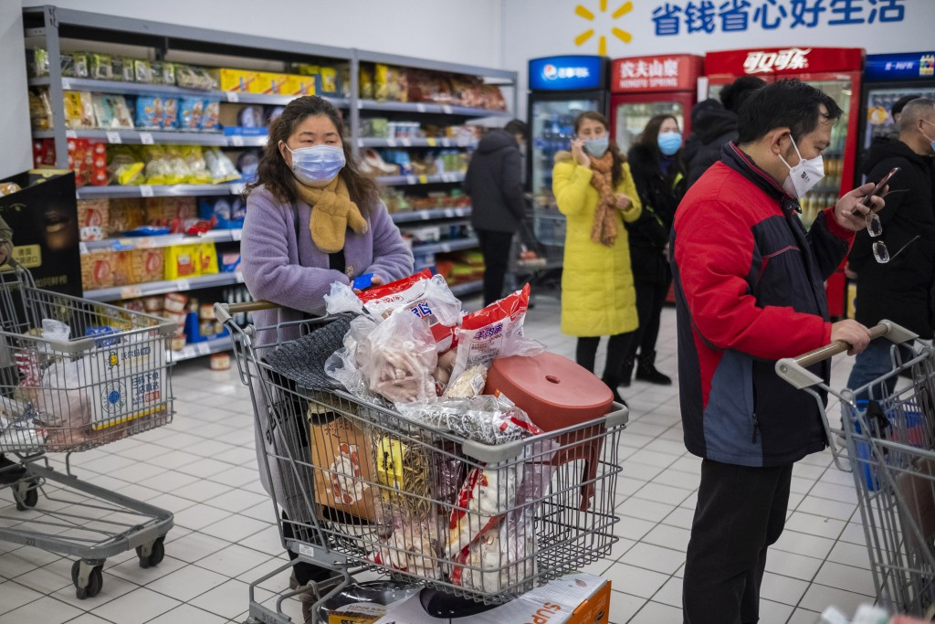 In this Jan. 22, 2020 photo, shoppers wear face masks as they line up at a grocery store in Wuhan in central China's Hubei Province. Complicated logis...