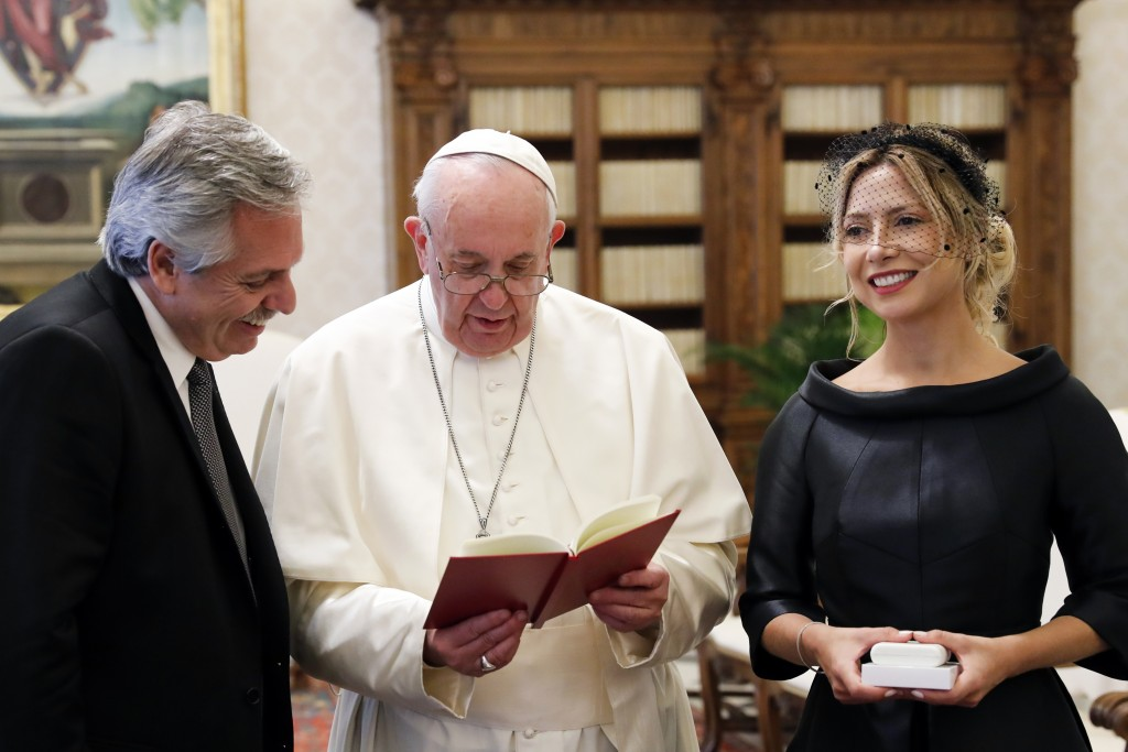 Pope Francis reads from his book Christus Vivit on the occasion of his private audience with Argentina's President Alberto Fernandez, left, and his pa...
