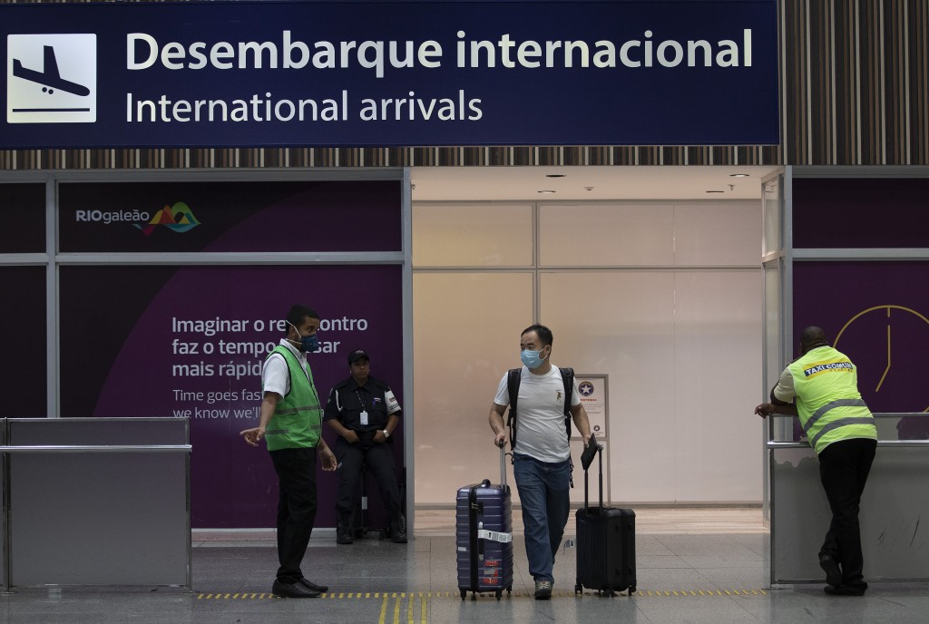 A passenger wearing a mask arrives to the Antonio Carlos Jobim Galeao International Airport, in Rio de Janeiro, Brazil, Friday, Jan. 31, 2020. Passeng...