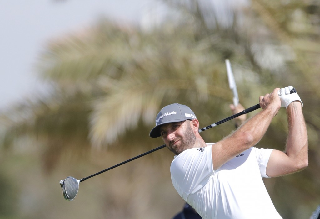 American Dustin Johnson follows his ball at the 6th hole during the third round of the Saudi International at Royal Greens Golf and Country Club, Satu...