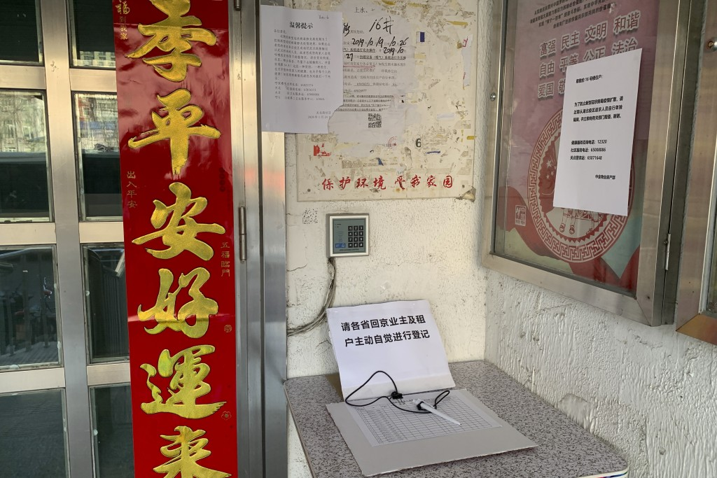 A registration book for residents who have recently returned from other provinces is displayed at the entrance to a neighborhood in Beijing, Friday, J...