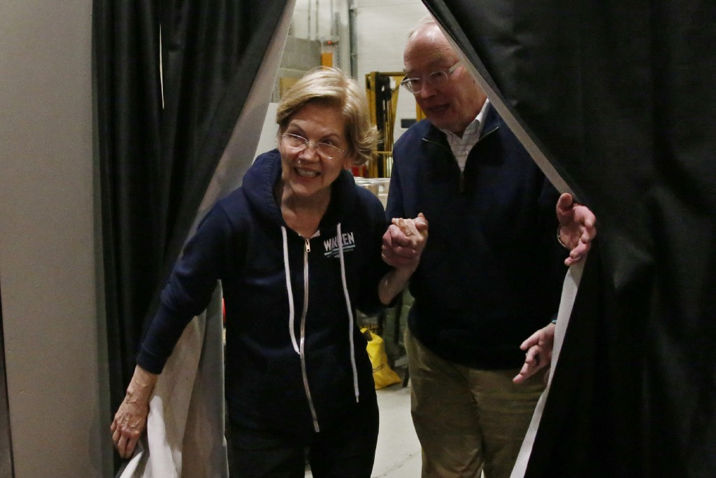 Democratic presidential candidate Sen. Elizabeth Warren, left, D-Mass., arrives with her husband, Bruce Mann, at a campaign event Friday, Jan. 31, 202...