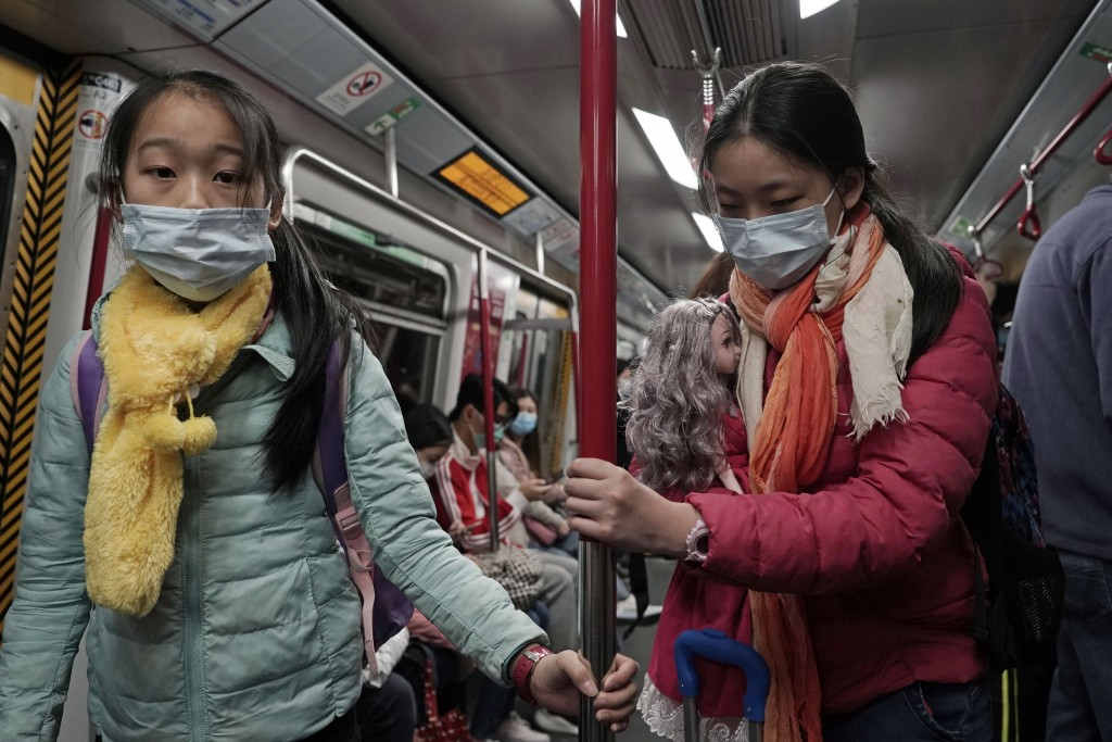 Two girls with face masks ride the subway in Hong Kong, Saturday, Feb, 1, 2020. China's death toll from a new virus has risen to 259 and a World Healt...