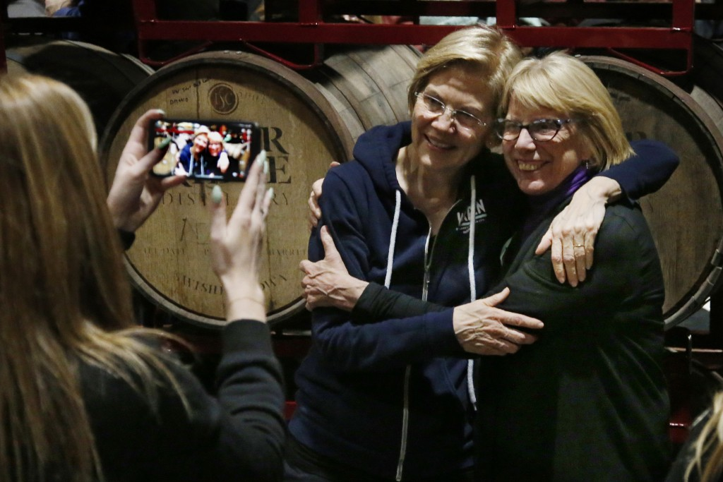 Democratic presidential candidate Sen. Elizabeth Warren, center, D-Mass., poses for a photo with a supporter at Peace Tree Brewing Co. Friday, Jan. 31...