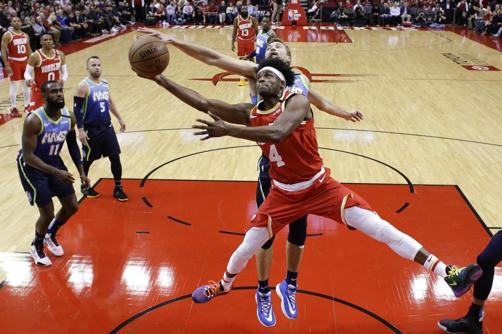 Houston Rockets forward Danuel House Jr. (4) shoots as Dallas Mavericks guard Ryan Broekhoff defends during the first half of an NBA basketball game F...