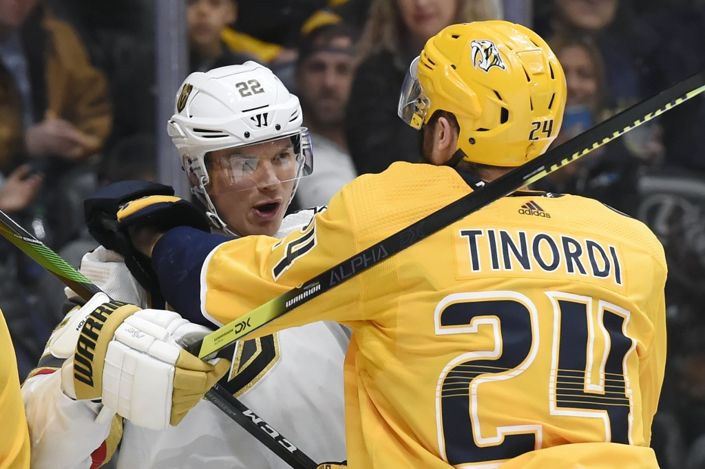Vegas Golden Knights defenseman Nick Holden (22) scuffles with Nashville Predators defenseman Jarred Tinordi (24) during the first period of an NHL ho...