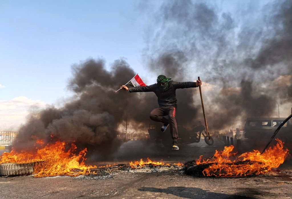An anti-government protester jumps over burning tires blocking a street during a demonstration against the newly appointed Prime Minister Mohammed All...