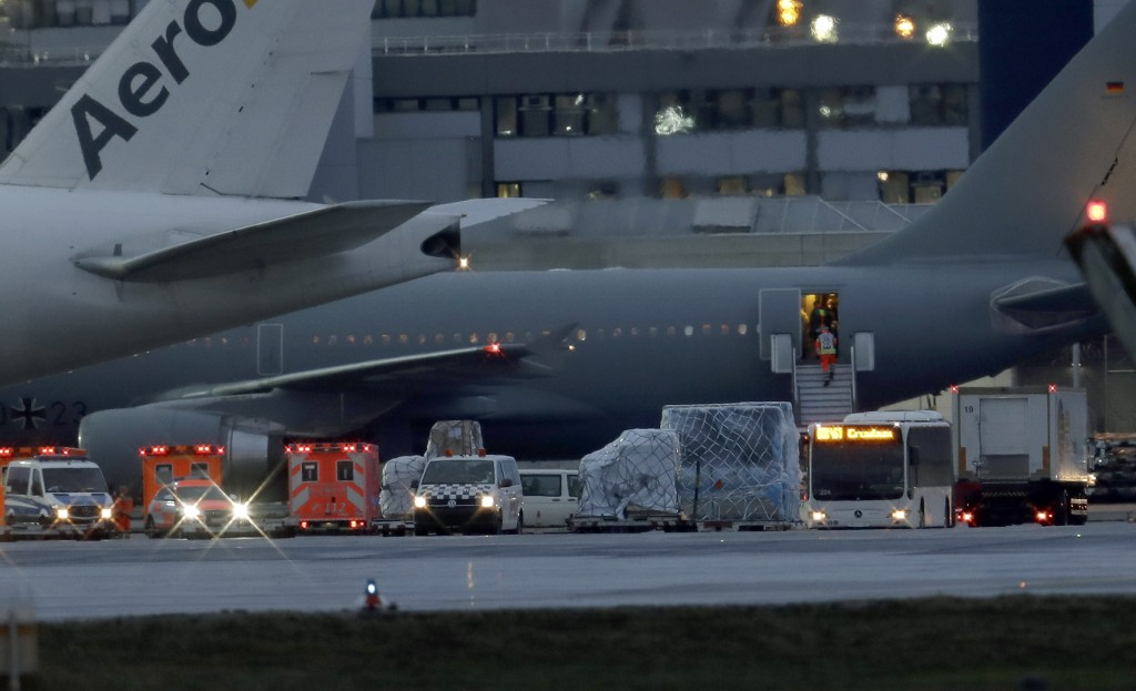 Ambulances and police cars stay next to an airplaine of the German air force with from China evacuated Germans aboard after its arrival at the Frankfu...
