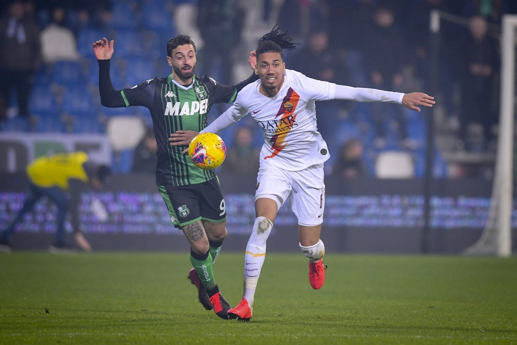 Roma's Chris Smalling, right, and Sassuolo's Francesco Caputo vie for the ball, during a Serie A soccer match between Roma and Sassuolo, in Reggio Emi...