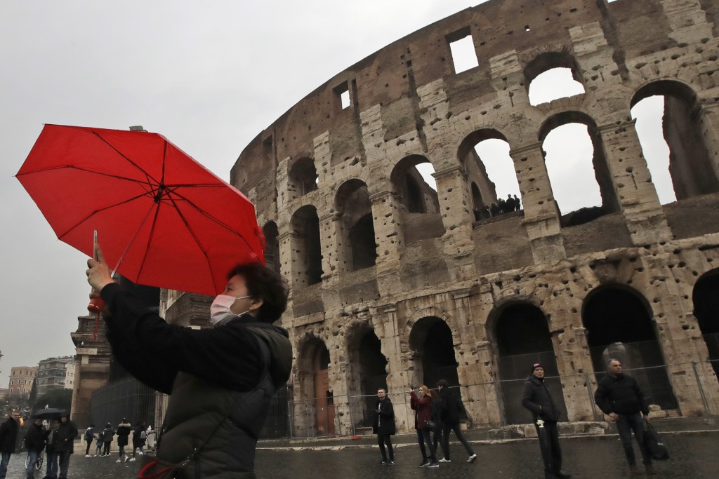 A tourist wearing a mask takes a selfie in front of Rome's ancient Colosseum, Saturday, Feb. 1, 2020. Italy banned all flights coming from and going t...