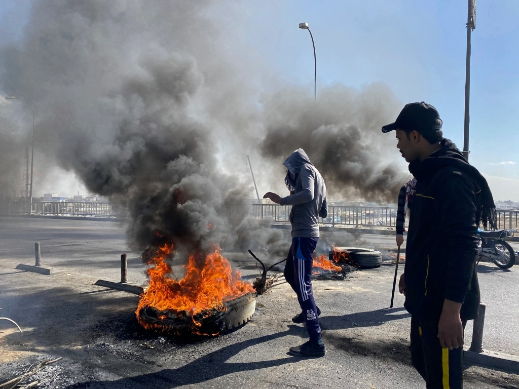 Smoke rises as anti-government protesters set fire to close a street during a demonstration against the newly appointed Prime Minister Mohammed Allawi...