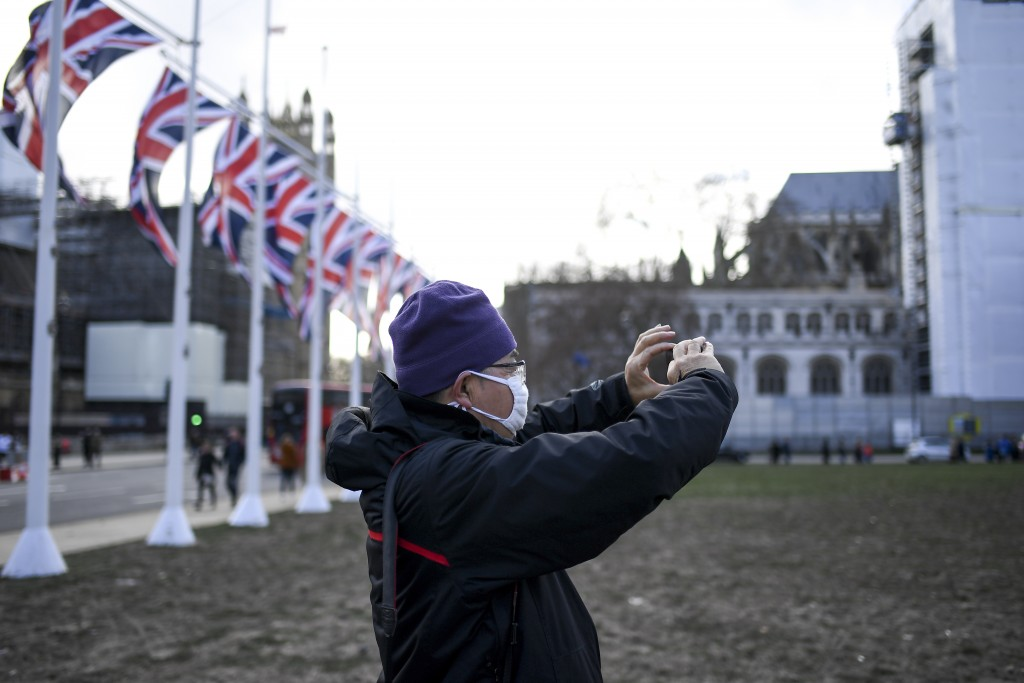 A man wearing a mask takes a picture in Parliament Square, in London, Saturday, Feb. 1, 2020. Two cases of coronavirus have been confirmed in Britain....