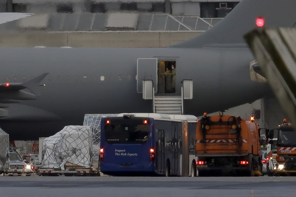 Two people wear a face mask as a bus stands next to an airplaine of the German air force with from China evacuated Germans aboard after its arrival at...