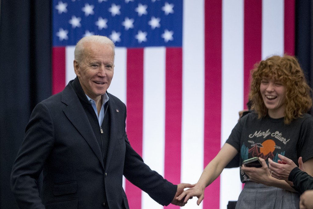 Democratic presidential candidate former Vice President Joe Biden shakes hands with a member of the audience as he arrives at a campaign stop at the S...