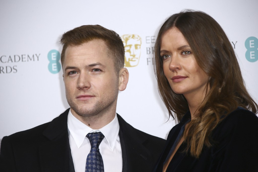 Actor Taron Egerton, left, and Emily Thomas pose for photographers upon arrival at the Bafta Nominees Party, in central London, Saturday, Feb. 1, 2020...