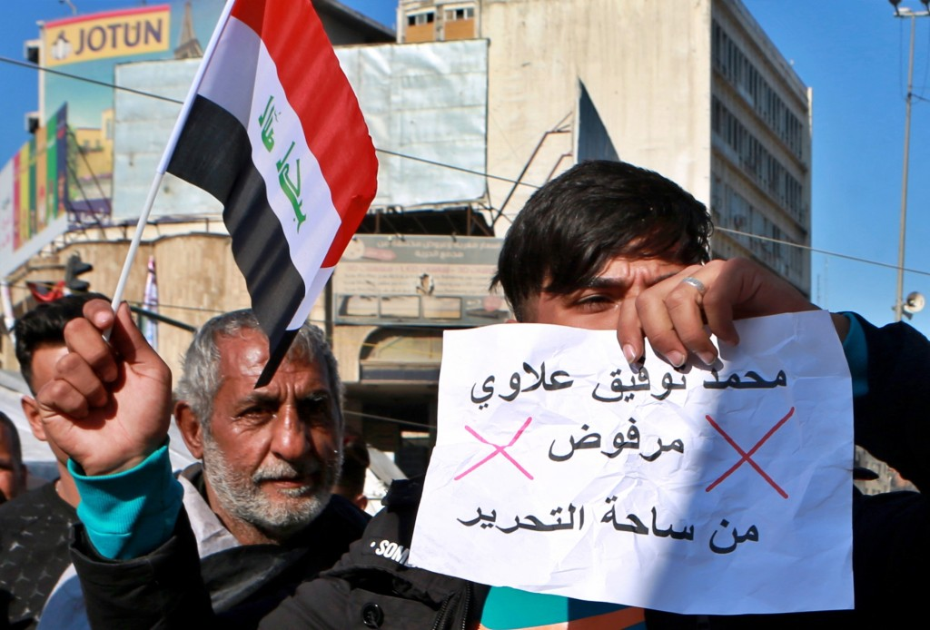 "An anti-government protester holds a national flag and a banner with Arabic that reads, ""Rejected"" during a demonstration against the newly appointed ..."