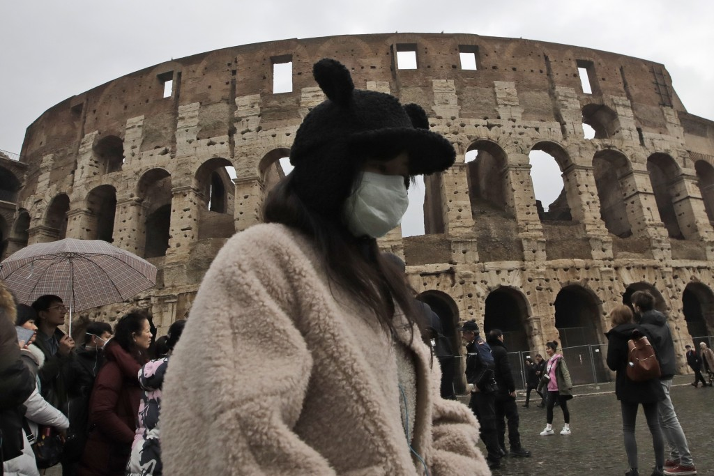 A tourist, part of a group coming from Shanghai, China, wears a mask as she visits Rome's ancient Colosseum, Saturday, Feb. 1, 2020. Italy banned all ...