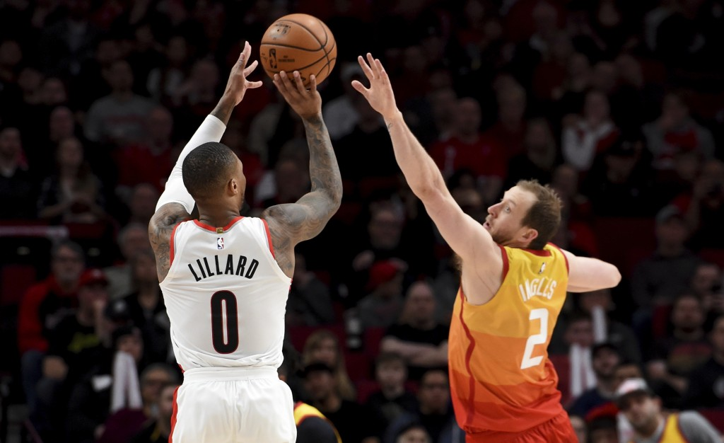 Portland Trail Blazers guard Damian Lillard, left, hits a shot over Utah Jazz guard Joe Ingles, right, during the second half of an NBA basketball gam...