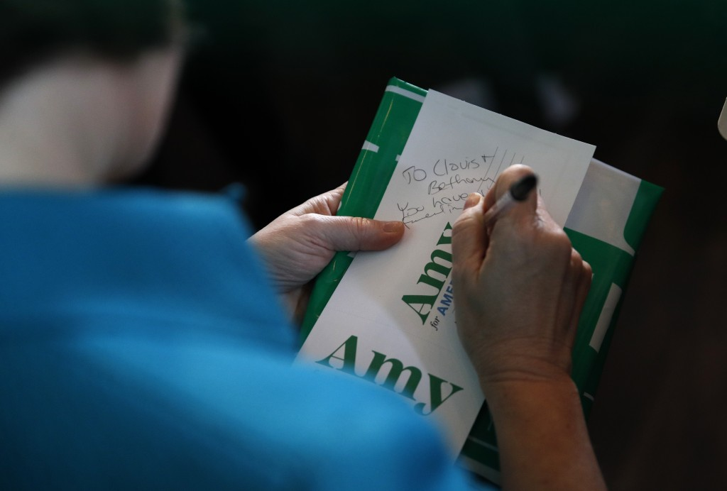 Democratic presidential candidate Sen. Amy Klobuchar, D-Minn., writes a note to an attendee during a campaign event at Crawford Brew Works, Saturday, ...