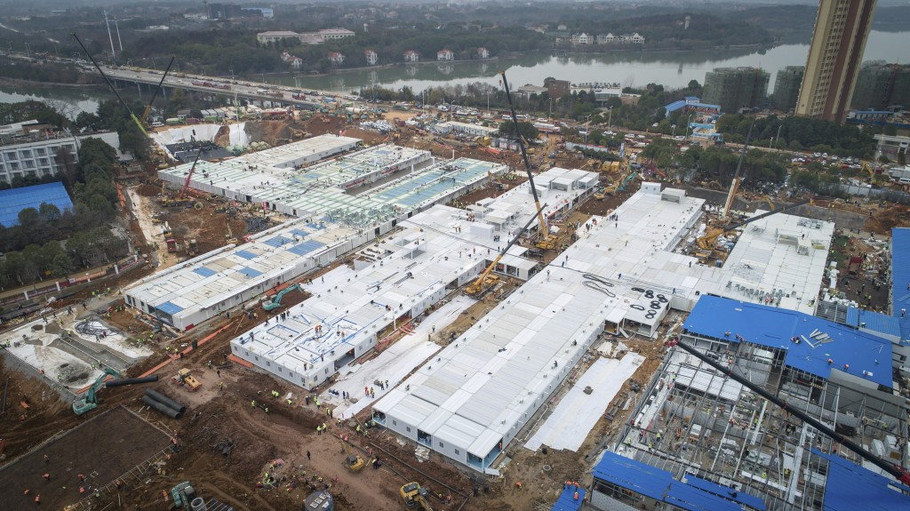 This Saturday, Feb. 1, 2020, photo released by China's Xinhua News Agency, shows construction workers at the site of the Huoshenshan temporary field h...