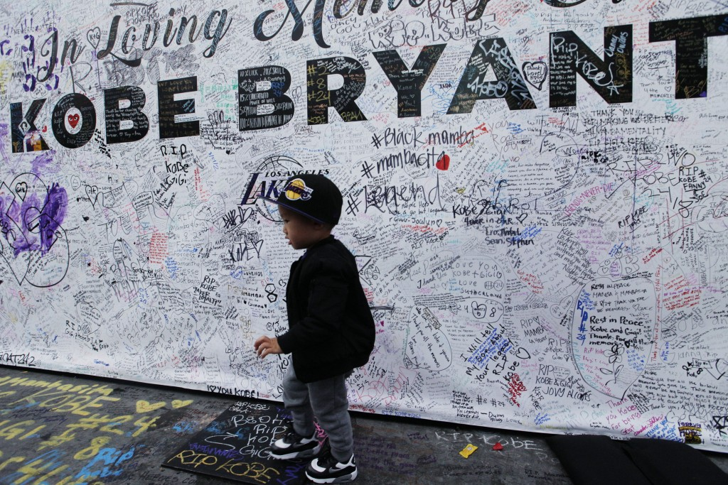 A boy walks by a standing board with messages for the late Kobe Bryant at a memorial for Bryant in front of Staples Center in Los Angeles Sunday, Feb....