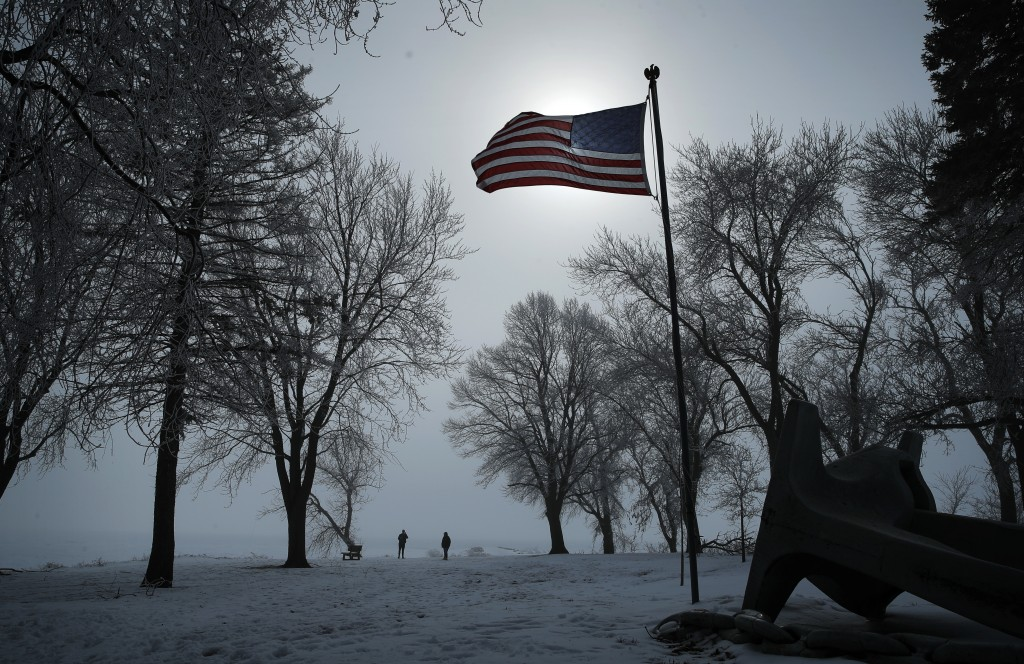 FILE - In this, Jan. 26, 2020, file photo, people walk along the shore of Storm Lake in Storm Lake, Iowa. (AP Photo/John Locher, File)