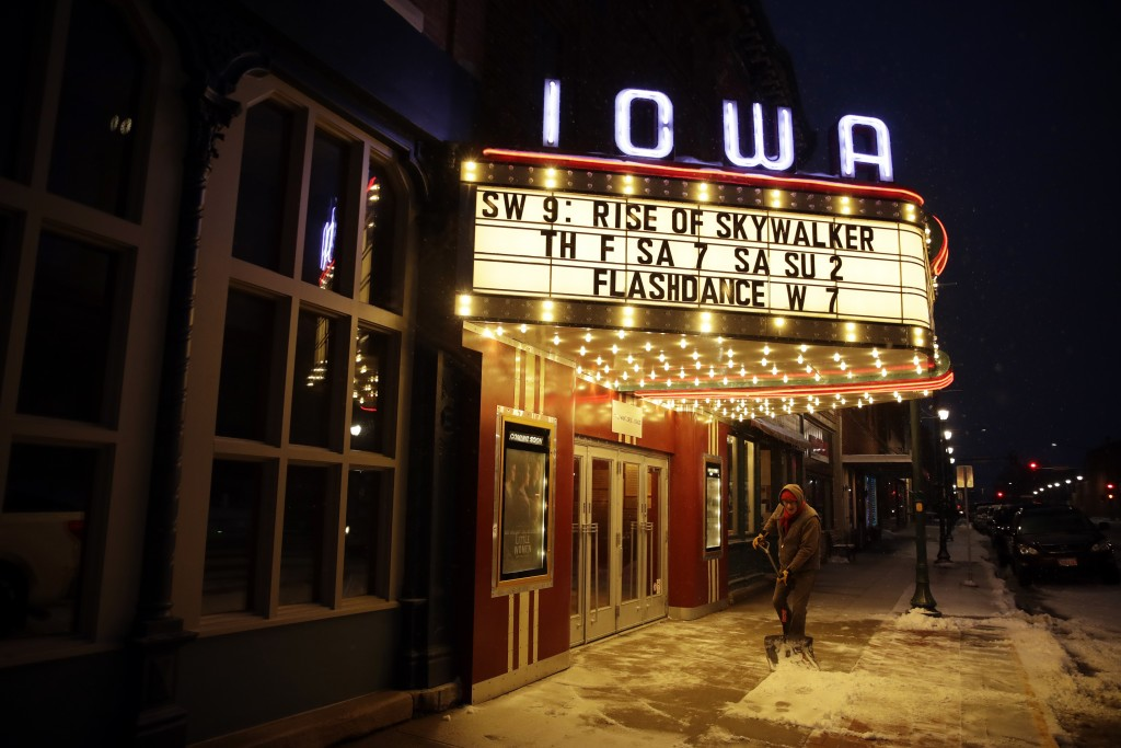 In this Jan. 24, 2020, photo, Scott Smith, manager of the Iowa Theater shovels snow from outside the theater's entrance in Winterset, Iowa. (AP Photo/...