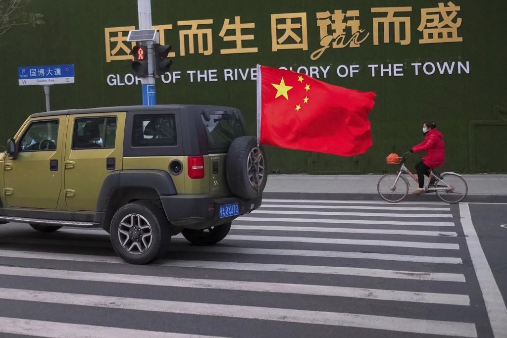 圖為中國湖北省武漢街頭上一婦女戴口罩行走的畫面(美聯社圖片)
