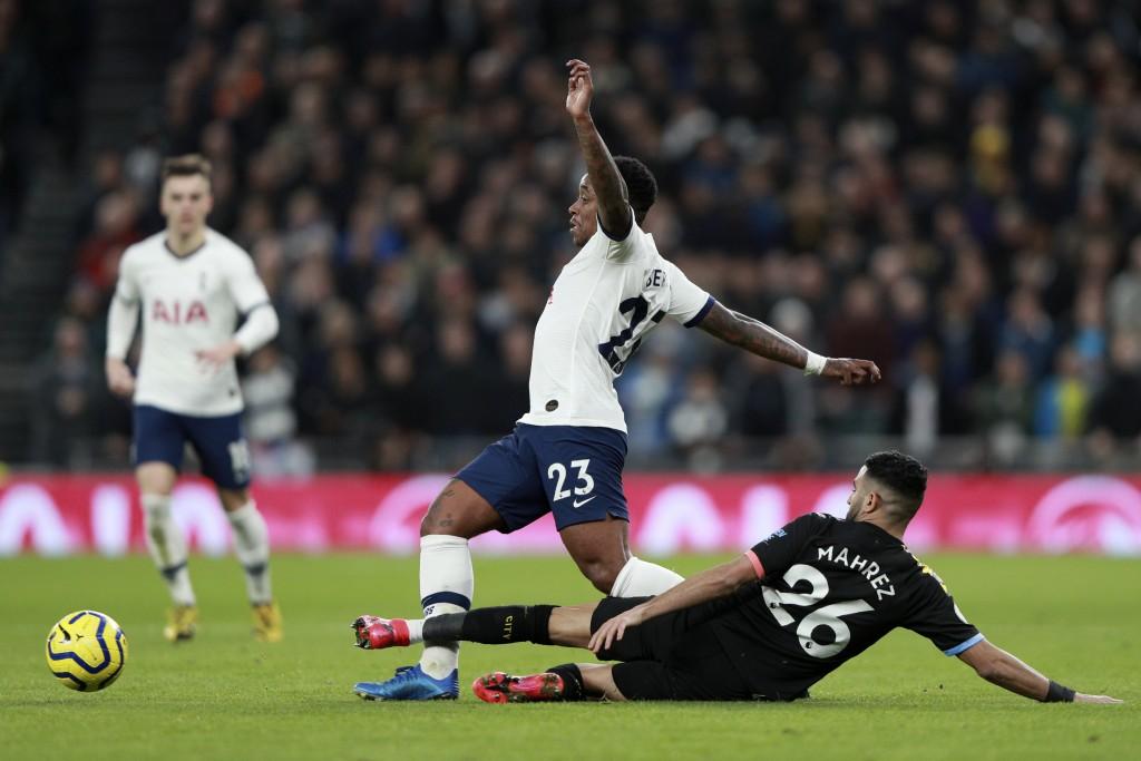 Manchester City's Riyad Mahrez, on the ground, tackles Tottenham's Steven Bergwijn during the English Premier League soccer match between Tottenham Ho...