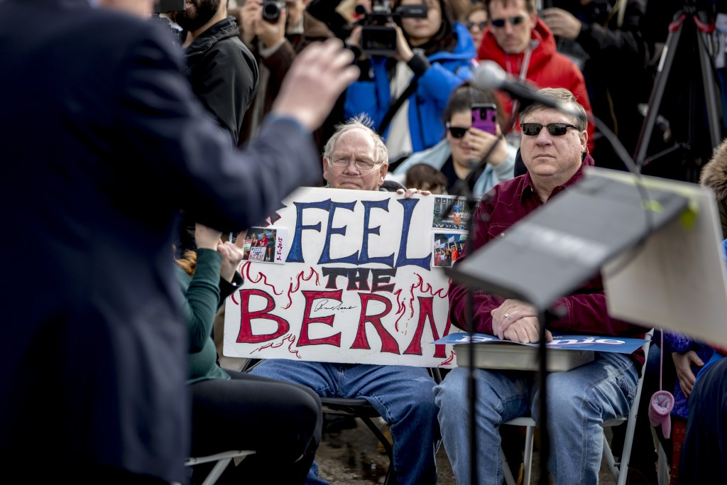 """A man with breathing tubes holds up a sign that reads """"Feel the Bern"""" as Democratic presidential candidate Sen. Bernie Sanders, I-Vt., left, speaks at..."""