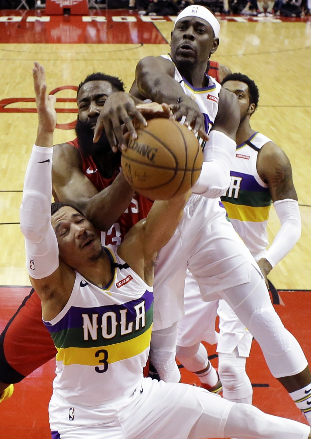 New Orleans Pelicans guards Josh Hart (3) and Jrue Holiday, top, vie with Houston Rockets guard James Harden, center, for a rebound during the first h...