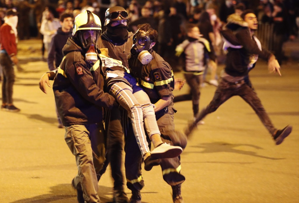 FILE - In this December 14, 2019 file photo, Civil defense workers carry an injured protester after a clash with riot police, in downtown Beirut, Leba...