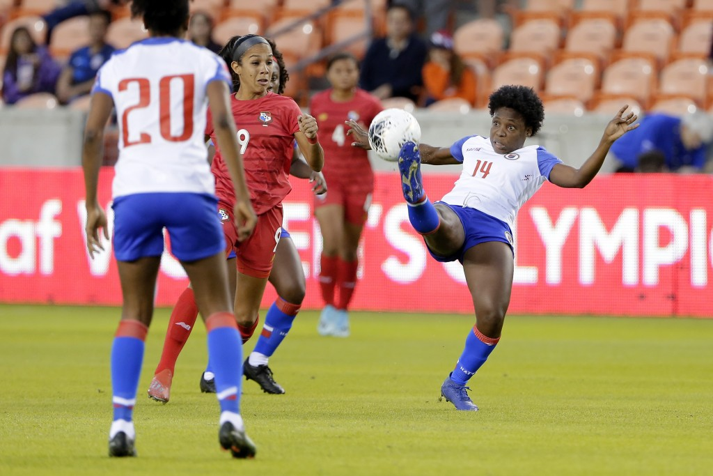 Haiti midfielder Phiseline Michel (14) kicks the ball away from Panama forward Amarelis De Mera (9) during the first half of a CONCACAF women's Olympi...