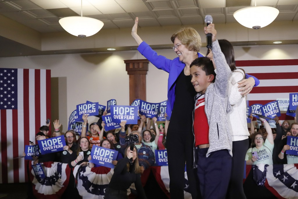 Democratic presidential candidate Sen. Elizabeth Warren, D-Mass., stands on stage with her grandchildren, Atticus Mann Tyagi, center, and Lavinia Tyag...