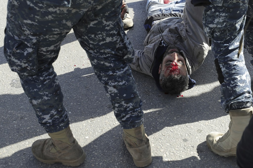 FILE - In this Monday, Jan. 27, 2020 file photo, police arrest an injured anti-government protester during a scuffle on the road leading to the parlia...