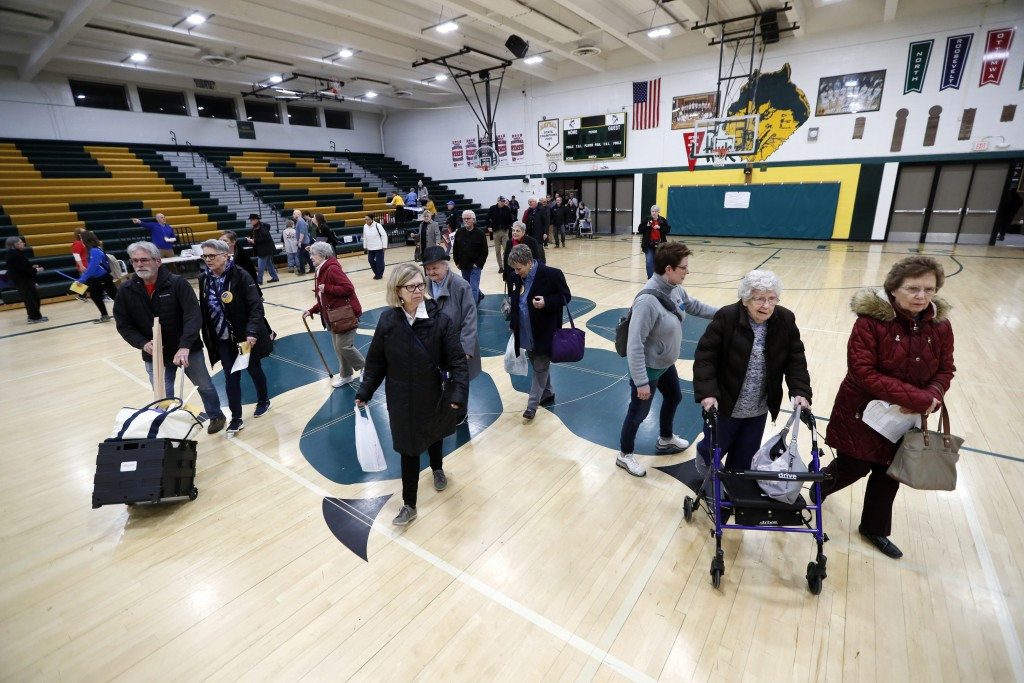 Local residents enter an Iowa Democratic caucus at Hoover High School, Monday, Feb. 3, 2020, in Des Moines, Iowa. (AP Photo/Charlie Neibergall)