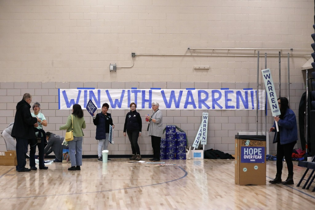 People prepare the gymnasium before a caucus at Roosevelt High School, Monday, Feb. 3, 2020, in Des Moines, Iowa. (AP Photo/Andrew Harnik)