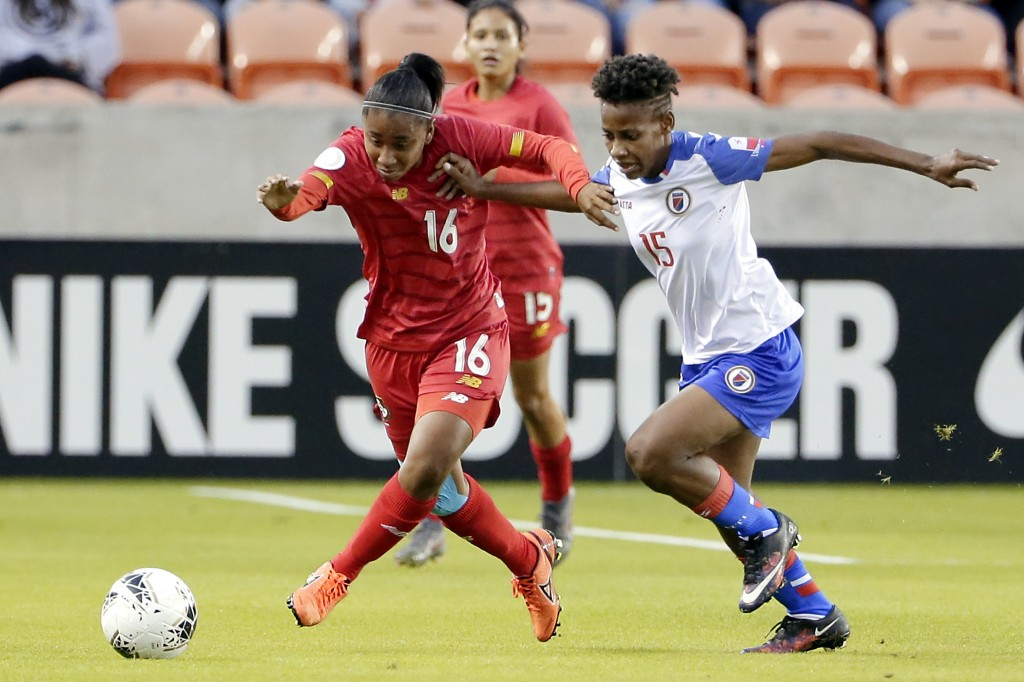 Panama midfielder Gloria Saenz (16) and Haiti defender Johane Laforte (15) push off each other as they chase the ball during the first half of a CONCA...