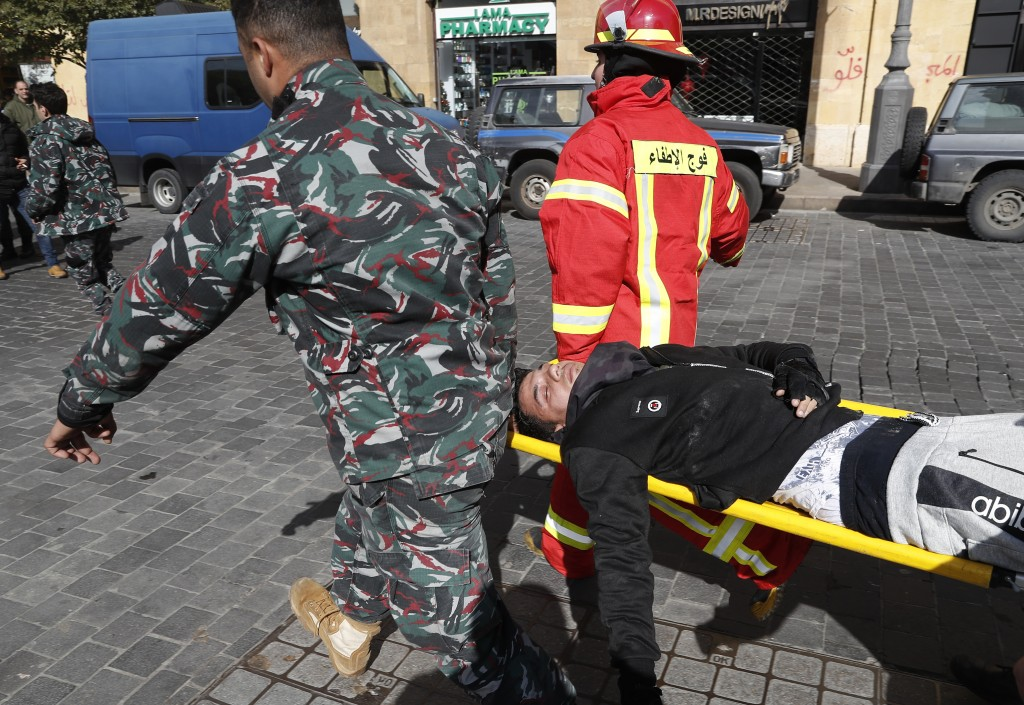 FILE - In this Jan. 27, 2020 file photo, a firefighter rescue team carries an anti-government protester who was injured in clashes in downtown Beirut,...