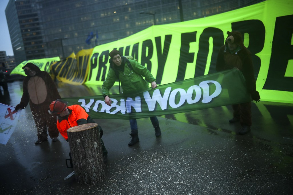 """Activists display banners during a climate change protest outside EU headquarters in Brussels, Tuesday, Feb. 4, 2020. The big banner reads: """"Save Euro..."""